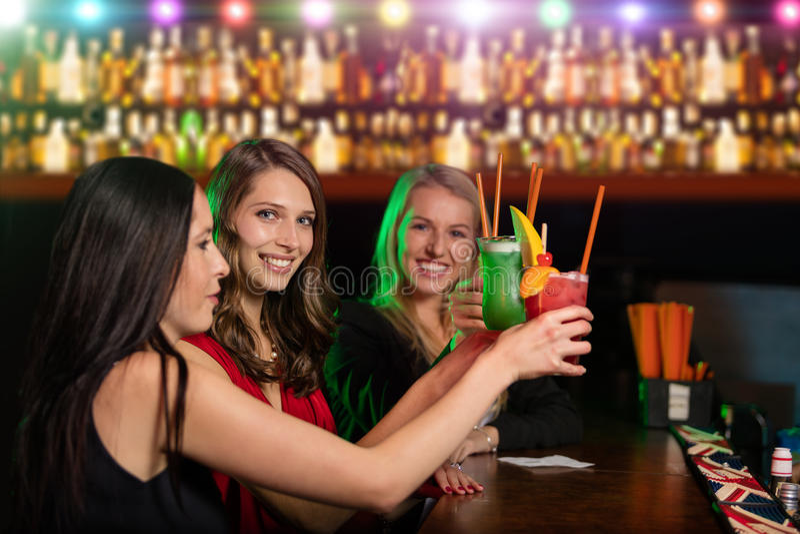 Groep vrienden bij de bar die hun glas opheffen van stock fotografie