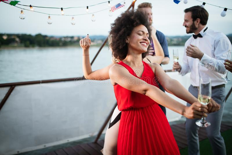 Groep vrienden bij en partij die samen dansen glimlachen royalty-vrije stock fotografie