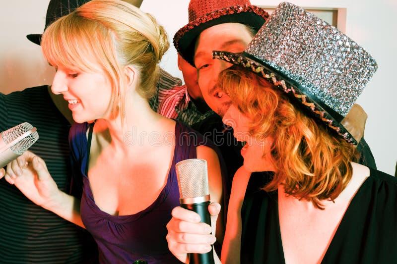 Groep vrienden bij karaokepartij royalty-vrije stock afbeelding