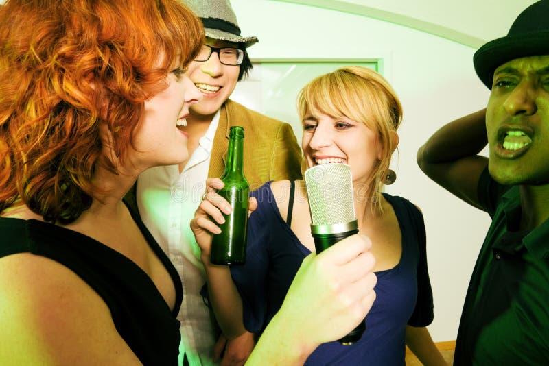 Groep vrienden bij karaokepartij stock afbeeldingen