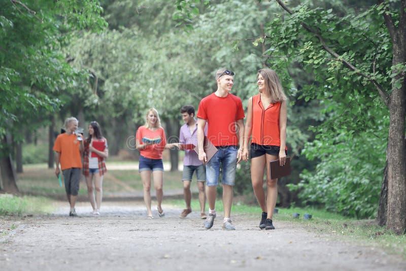 Groep vrienden bij park die en van tijd samen lopen genieten allen stock foto