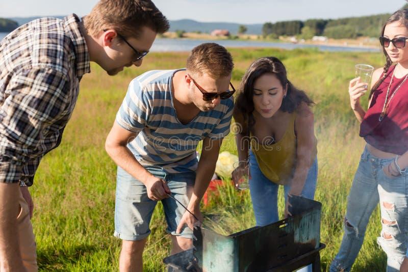 Groep vrienden die BBQ hebben bij meer in de zomer stock afbeelding