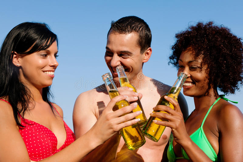 Groep vrienden die bier in swimwear drinken stock fotografie
