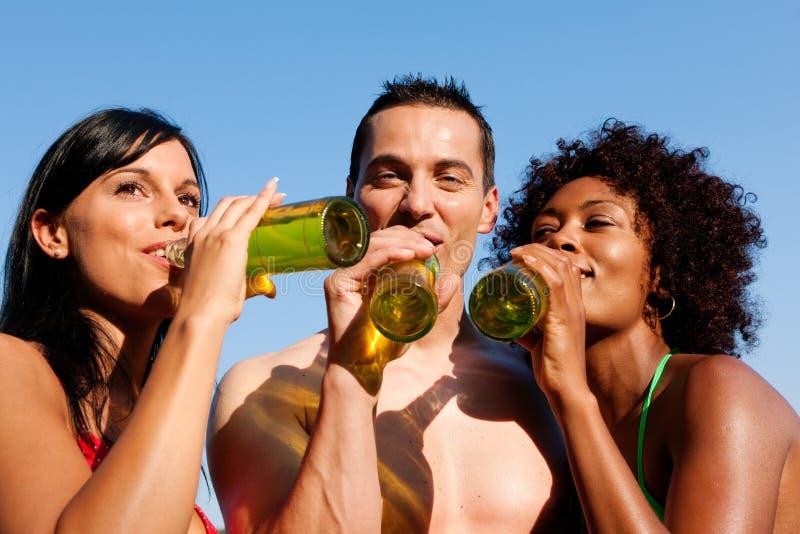 Groep vrienden die bier in swimwear drinken stock afbeeldingen