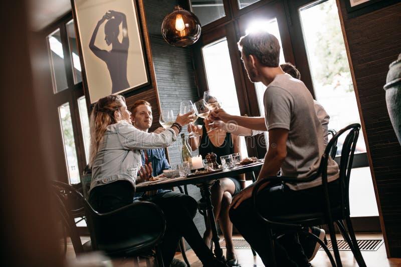 Groep vrienden die bij restaurant roosteren stock foto's