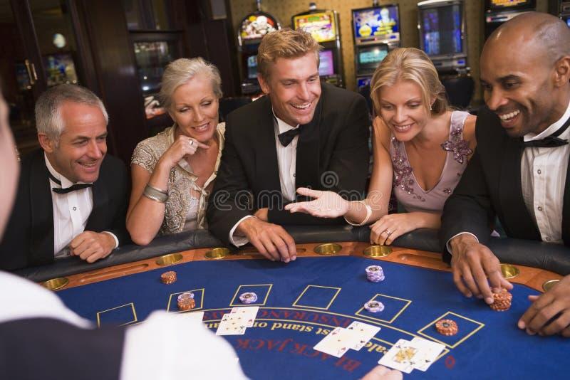 Groep vrienden die blackjack in casino spelen royalty-vrije stock fotografie