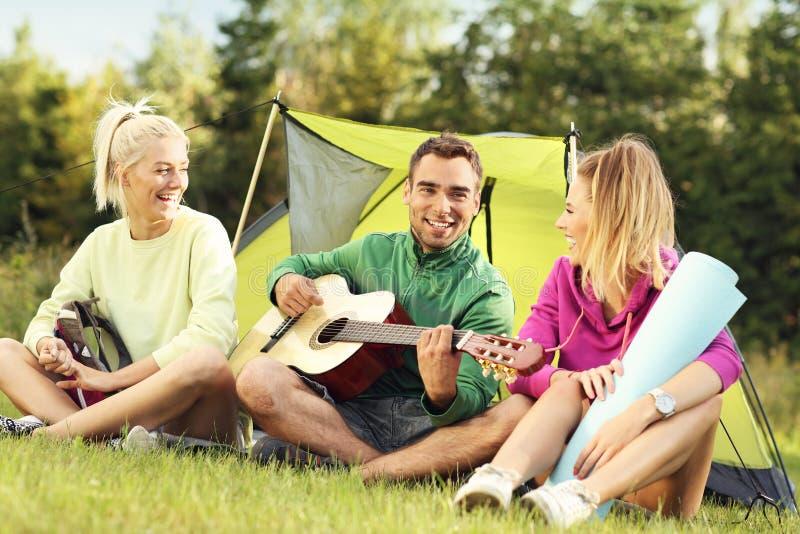Groep vrienden die in bos en het spelen gitaar kamperen stock foto