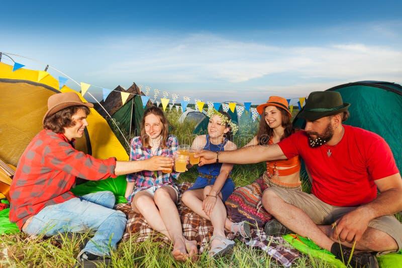 Groep vrienden die buiten hun tenten drinken royalty-vrije stock afbeeldingen