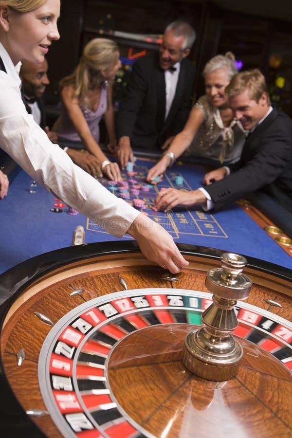 Groep vrienden die in casino gokken stock afbeeldingen