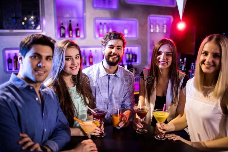Groep vrienden die cocktail hebben bij barteller stock fotografie