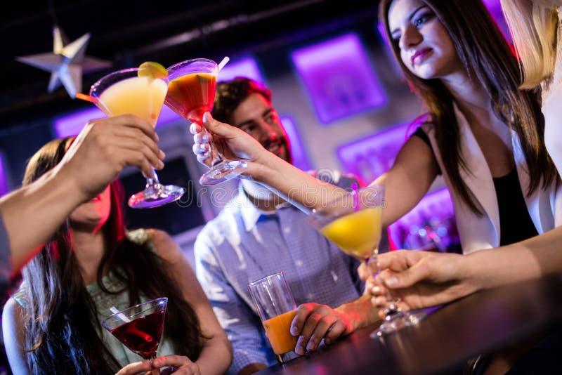 Groep vrienden die cocktail roosteren bij barteller stock foto's