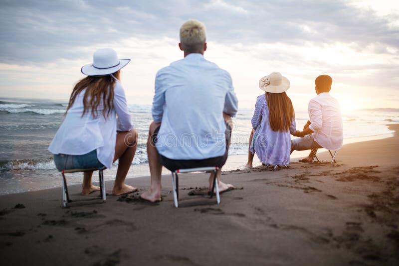 Groep vrienden die de zomer van vakantie genieten bij zonsondergang op strand royalty-vrije stock foto's