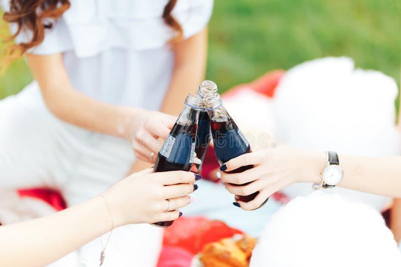 Groep vrienden die dranken houden bij de de zomerpicknick Sluit omhoog Maak chears zwarte limonade in glasflessen stock fotografie