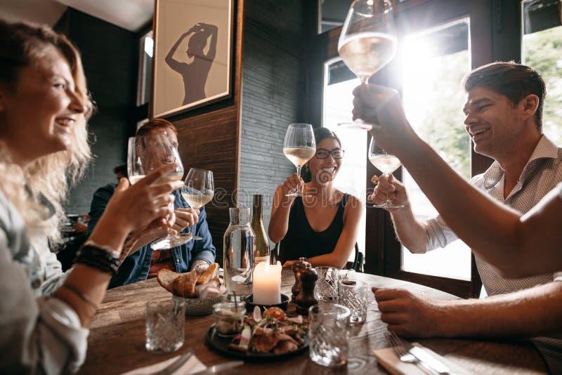 Groep vrienden die een toost maken bij restaurant royalty-vrije stock fotografie