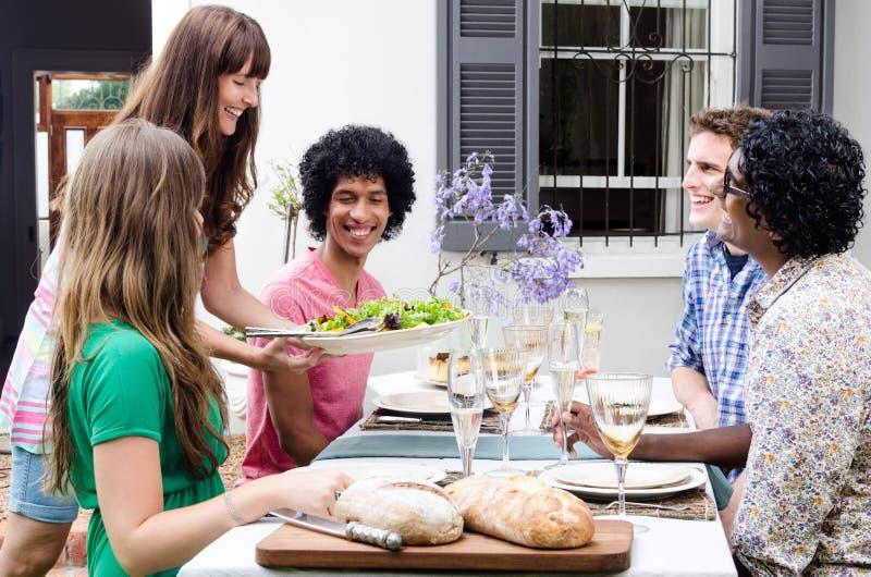 Groep vrienden die en bij lunch glimlachen lachen stock fotografie