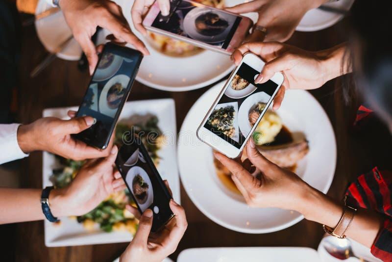Groep vrienden die en een foto van Italiaans voedsel samen met mobiele telefoon nemen uitgaan royalty-vrije stock fotografie