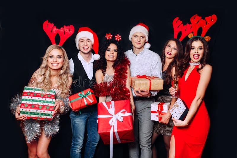 Groep vrienden die en Kerstmisgiften delen lachen Vrienden die Kerstmis of Nieuwjaarvooravondpartij vieren royalty-vrije stock fotografie