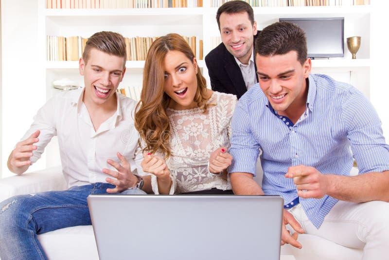 Groep vrienden die en op bij laptop letten samenwerken stock fotografie