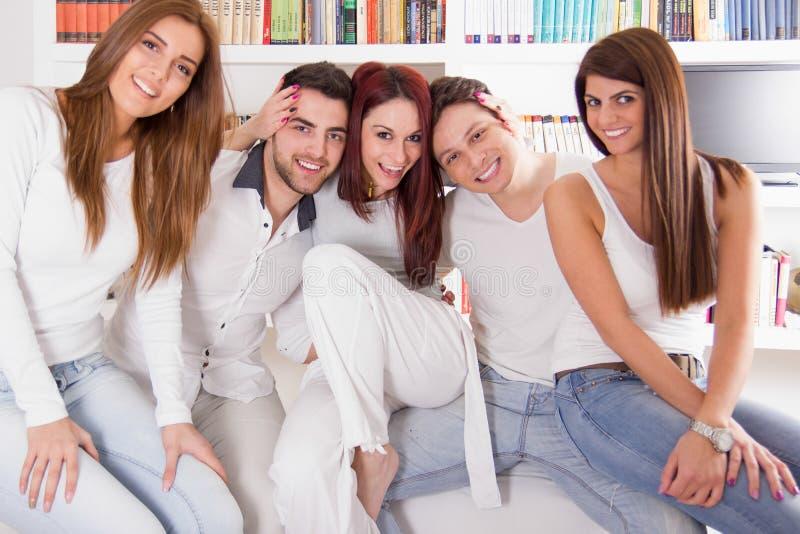 Groep vrienden die en samen op bank thuis glimlachen zitten stock afbeelding