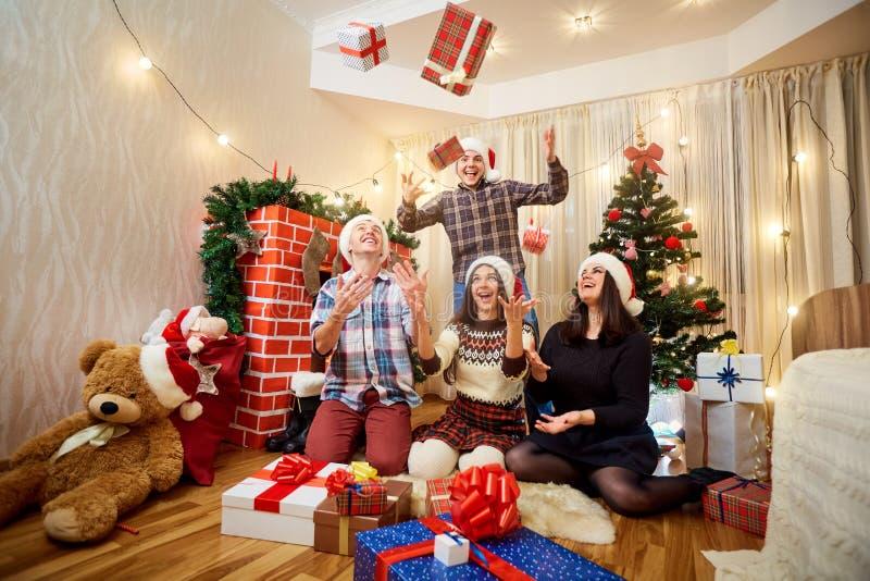 Groep vrienden die in gelukkige Kerstmisgiften, hebbend fu lachen royalty-vrije stock fotografie