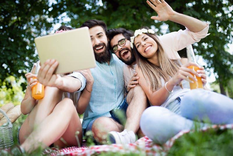 Groep vrienden die grote tijd op picknick in aard hebben stock afbeeldingen