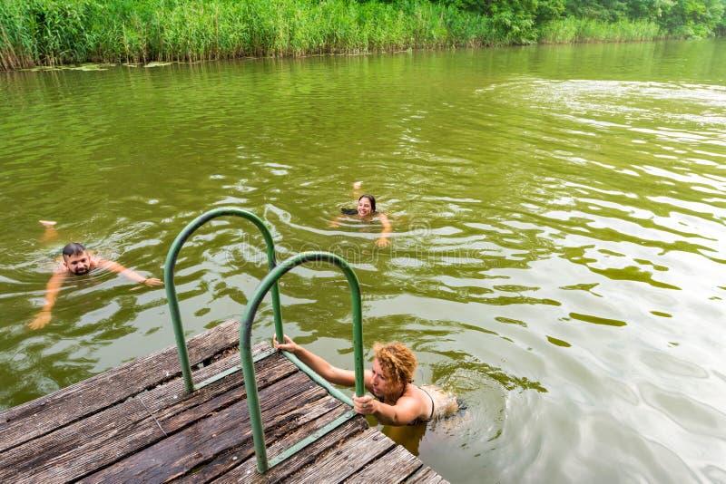 Groep vrienden die in het meer zwemmen stock foto
