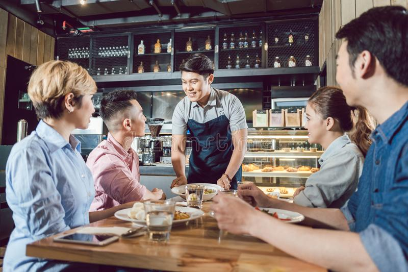 Groep vrienden die kelners dienend voedsel bekijken royalty-vrije stock foto