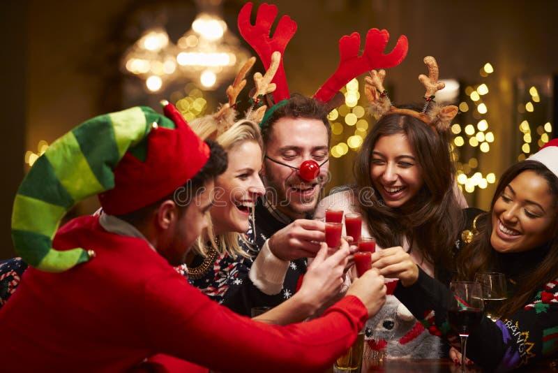 Groep Vrienden die Kerstmis van Dranken in Bar genieten stock foto's