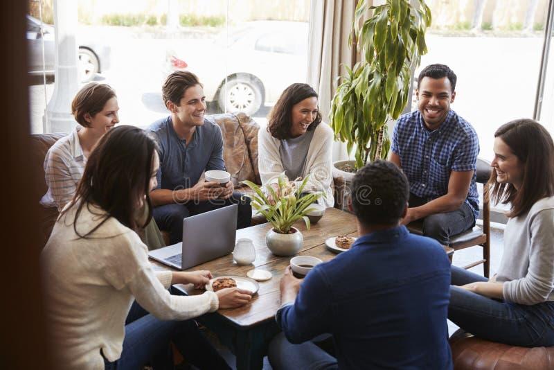 Groep vrienden die koffie hebben samen bij een koffiewinkel royalty-vrije stock foto
