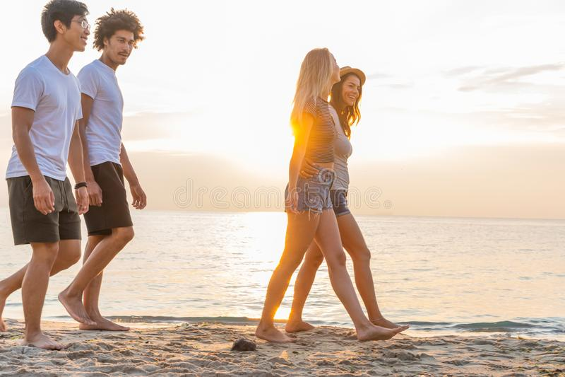 Groep vrienden die langs een strand bij zomer lopen Gelukkige jongeren die van een dag genieten bij strand stock afbeeldingen