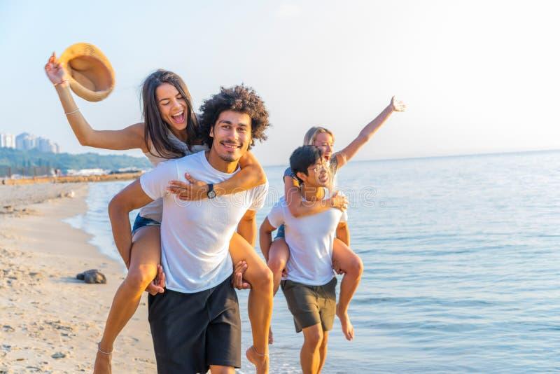 Groep vrienden die langs het strand, met mensen lopen die op de rug rit geven aan meisjes Gelukkige jonge vrienden die van a geni royalty-vrije stock afbeeldingen