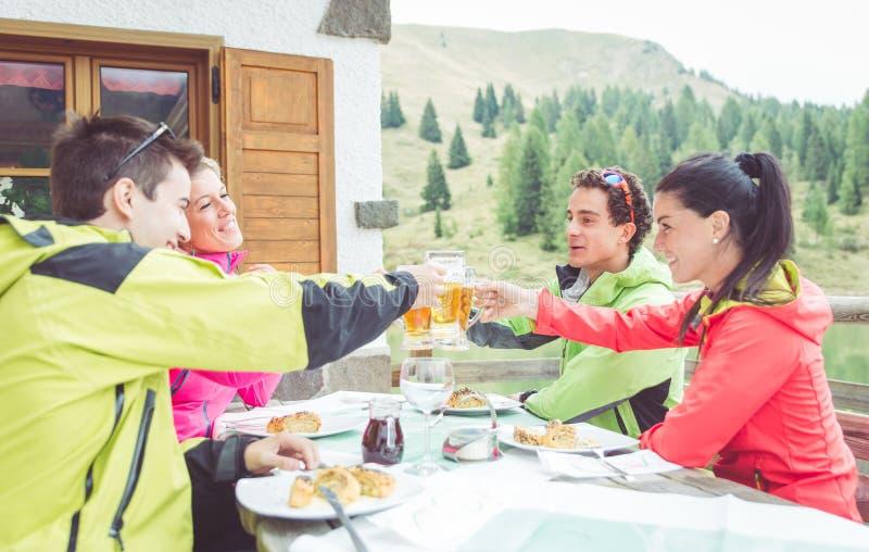 Groep vrienden die met bieren roosteren stock fotografie