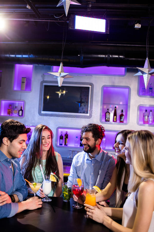 Groep vrienden die met elkaar bij barteller interactie aangaan terwijl het hebben van cocktail stock foto