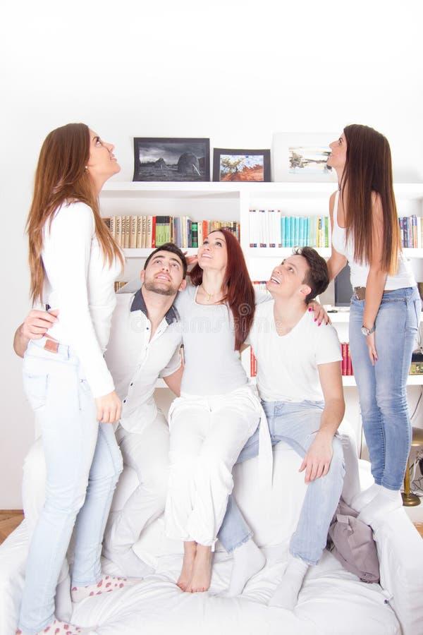 Groep vrienden die omhoog binnen met erachter boeken kijken royalty-vrije stock foto's