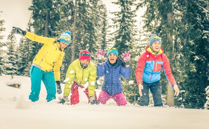 Groep vrienden die op de sneeuw spelen stock foto's