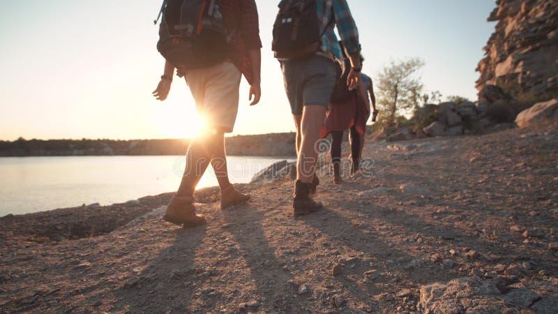 Groep vrienden die op rotsachtige kustlijn wandelen royalty-vrije stock afbeeldingen