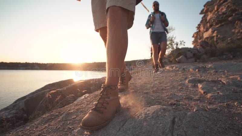 Groep vrienden die op rotsachtige kustlijn wandelen stock foto's