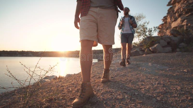 Groep vrienden die op rotsachtige kustlijn wandelen stock afbeelding