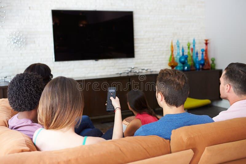 Groep Vrienden die op Sofa Watching-TV samen zitten royalty-vrije stock afbeeldingen