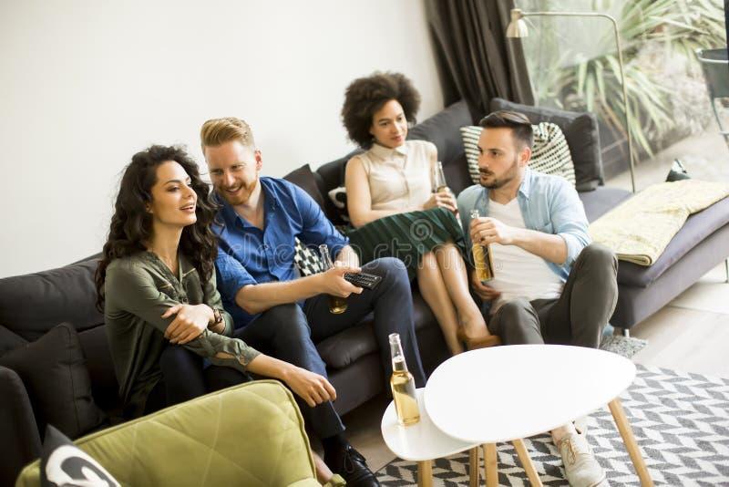 Groep vrienden die op TV letten, cider drinken en pret hebben stock fotografie