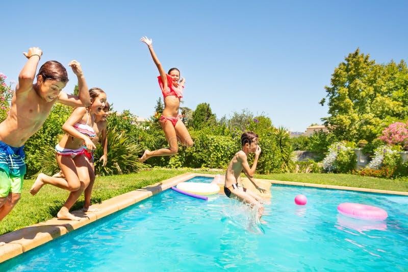Groep vrienden die in openlucht zwembad springen stock afbeeldingen