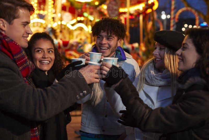 Groep Vrienden die Overwogen Wijn drinken bij Kerstmismarkt stock foto's