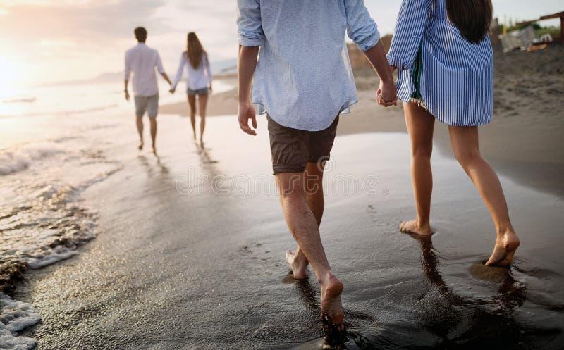 Groep vrienden die pret hebben en op het strand bij zonsondergang lopen stock foto