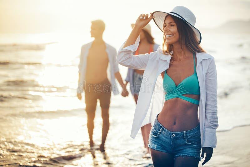 Groep vrienden die pret hebben en op het strand bij zonsondergang lopen royalty-vrije stock afbeeldingen