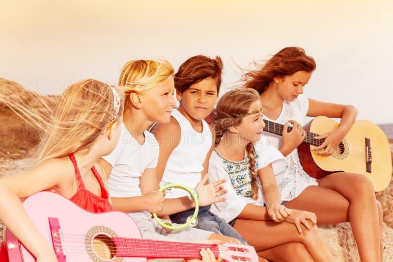 Groep vrienden die pret met gitaar hebben openlucht royalty-vrije stock foto