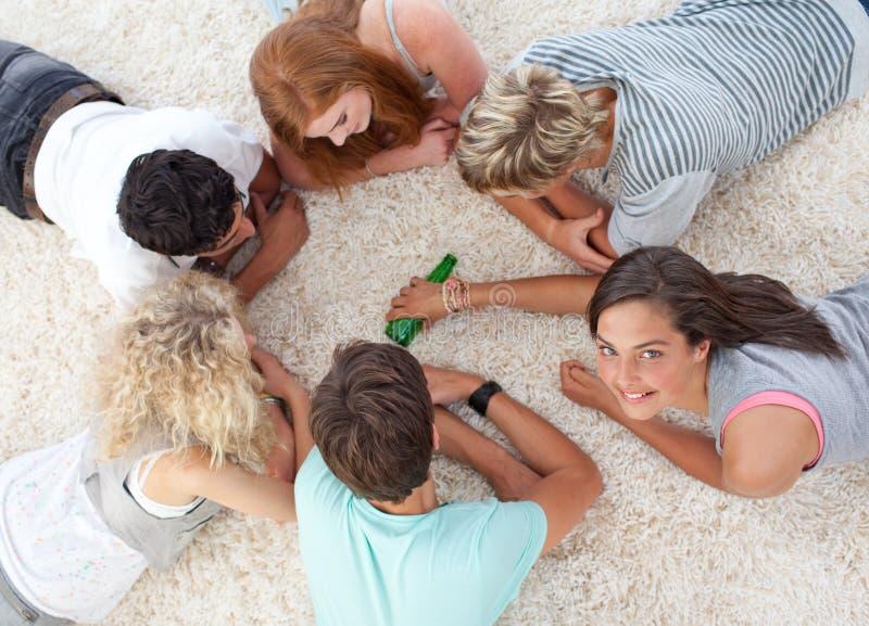Groep vrienden die rotatie spelen de fles stock foto's