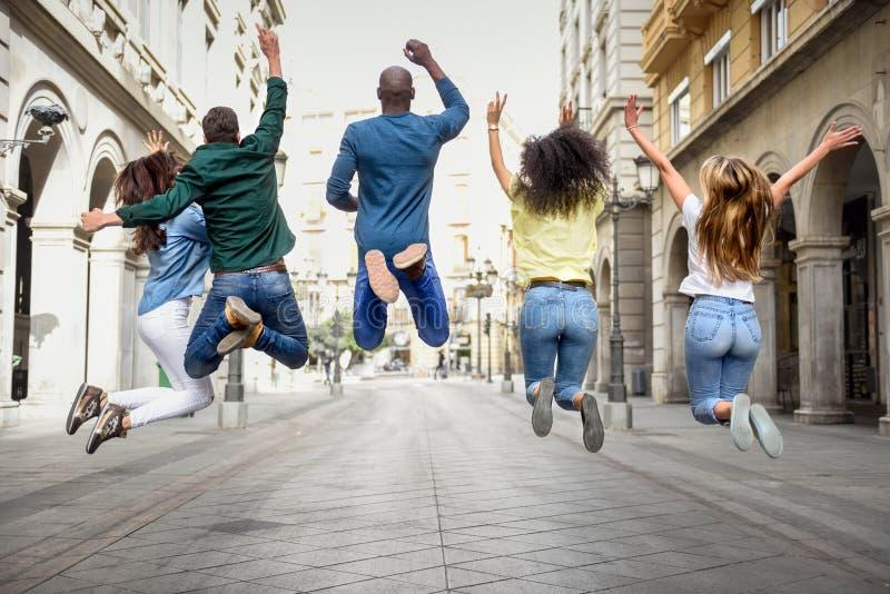 Groep vrienden die samen in openlucht springen royalty-vrije stock foto