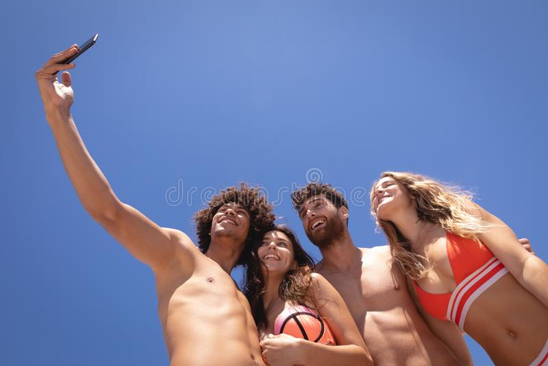 Groep vrienden die selfie met mobiele telefoon bij strand in de zonneschijn nemen royalty-vrije stock foto's