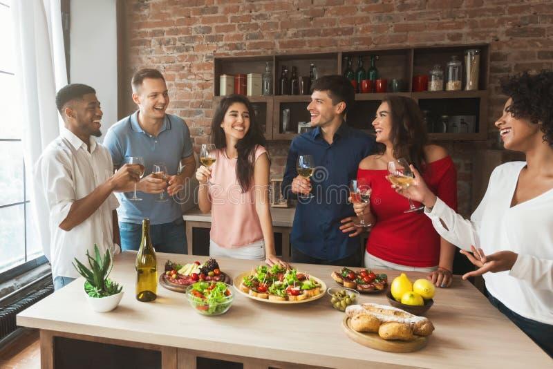 Groep vrienden die tijdens huispartij spreken stock afbeeldingen