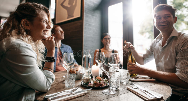 Groep vrienden die van een avondmaaltijd genieten bij een restaurant royalty-vrije stock fotografie
